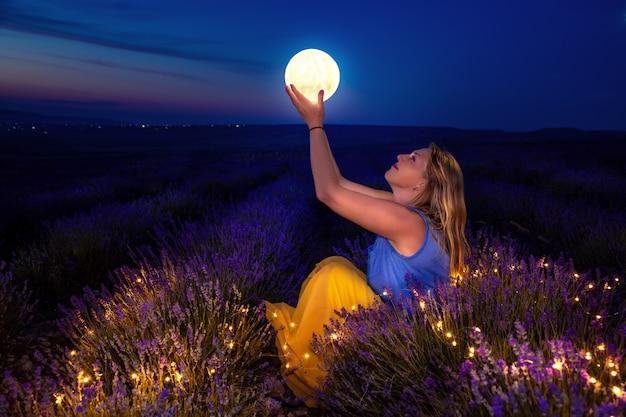 La ragazza tiene la luna tra le mani. campo di lavanda di notte.