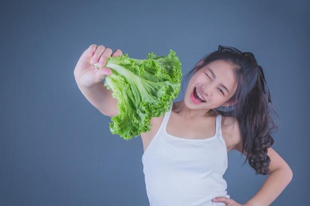 La ragazza tiene le verdure su uno sfondo grigio.