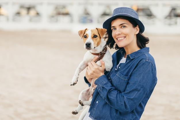 La ragazza tiene un cane in braccio su una spiaggia sabbiosa