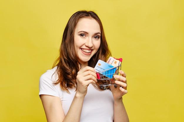 La ragazza tiene un carrello della spesa con carte di credito