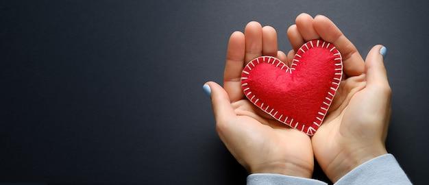La ragazza tiene un cuore fatto a mano rosso su sfondo nero. banner.