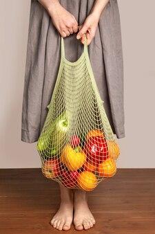 La ragazza tiene un sacchetto di spago con frutta e verdura. il concetto di shopping verde e buona alimentazione. consegna dei prodotti. protezione ambientale.