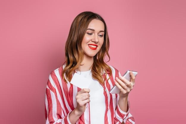 La ragazza tiene un telefono cellulare e una carta di credito, esamina lo schermo del telefono isolato sopra fondo rosa