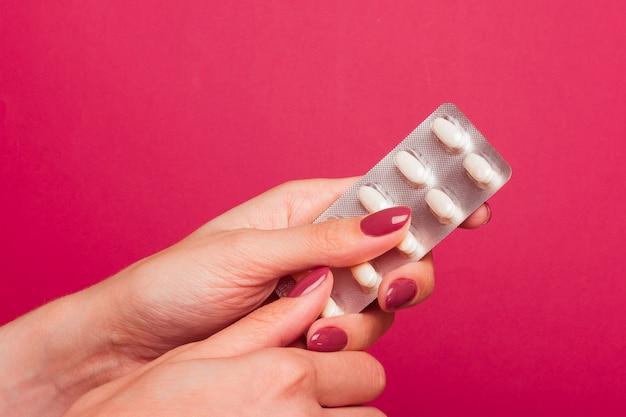 La ragazza tiene una bolla con le pillole. rimuove una compressa da un blister. sfondo medico rosa affascinante.