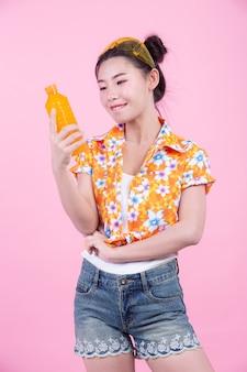 La ragazza tiene una bottiglia di succo d'arancia su uno sfondo rosa.