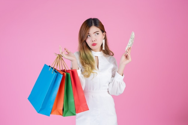 La ragazza tiene una shopping bag di moda e tiene un biglietto da un dollaro
