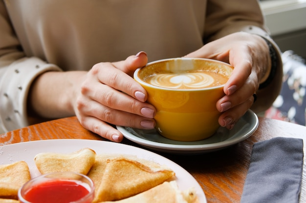 La ragazza tiene una tazza di caffè su un tavolo di legno nel caffè. accanto a un piatto di frittelle e marmellata. pausa caffè, colazione