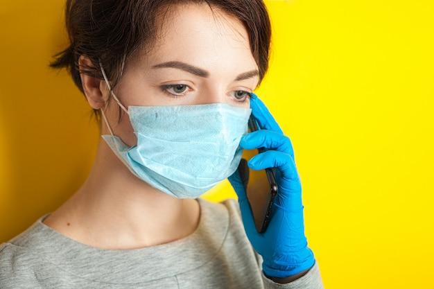 La ragazza triste in una maschera e guanti medici tiene un telefono cellulare