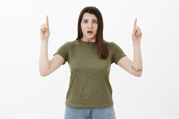 La ragazza triste preoccupata e confusa non riesce a capire cosa sia successo aggrottando le sopracciglia a bocca aperta per la frustrazione e lo shock, guardando nervosamente mentre indicava con le mani alzate sopra il muro grigio