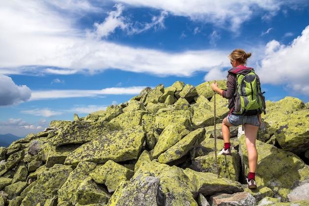 La ragazza turistica bionda atletica esile della viandante con l'arrampicata dello zaino e del bastone si è accesa dall'alta montagna rocciosa del sole su cielo blu luminoso. turismo, viaggi, escursioni e concetto di stile di vita sano.