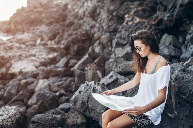 La ragazza turistica dei capelli abbastanza lunghi che si rilassa sulle pietre si avvicina al mare