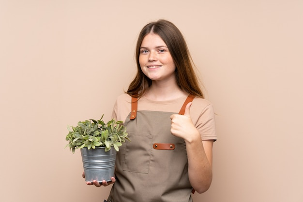 La ragazza ucraina del giardiniere dell'adolescente che tiene una pianta che dà pollici aumenta il gesto