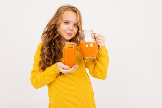 La ragazza versa il succo di carota da una brocca in un vetro