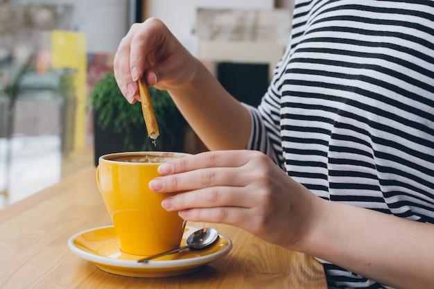 La ragazza versa lo zucchero da una borsa in una tazza di caffè