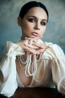 La ragazza vestita in abiti bianchi boho con perle bianche intorno al collo è seduta a un tavolo. sorriso perfetto, romantica immagine sexy di una donna, pelle pulita e liscia e bel trucco