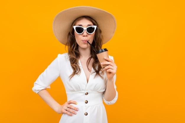 La ragazza vestita in un abito bianco con un cappello i in bicchieri beve un drink su uno sfondo giallo