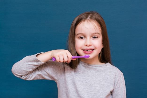 La ragazza vuole spazzare via i denti da latte cadenti su un fondo blu. il concetto di igiene orale e denti da latte nei bambini
