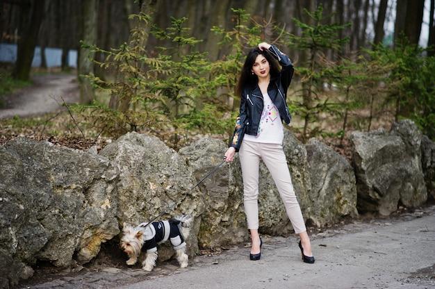 La ragazza zingara castana con il cane dell'yorkshire terrier ha posato contro le pietre sul parco. modello indossa giacca di pelle con ornamenti, pantaloni e scarpe con tacchi alti.