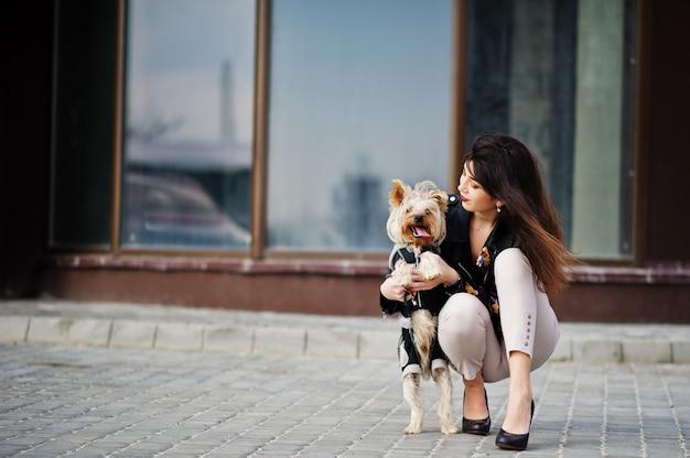 La ragazza zingara castana con il cane dell'yorkshire terrier ha proposto contro la grande casa delle finestre. modello indossa giacca di pelle con ornamenti, pantaloni e scarpe con tacchi alti.