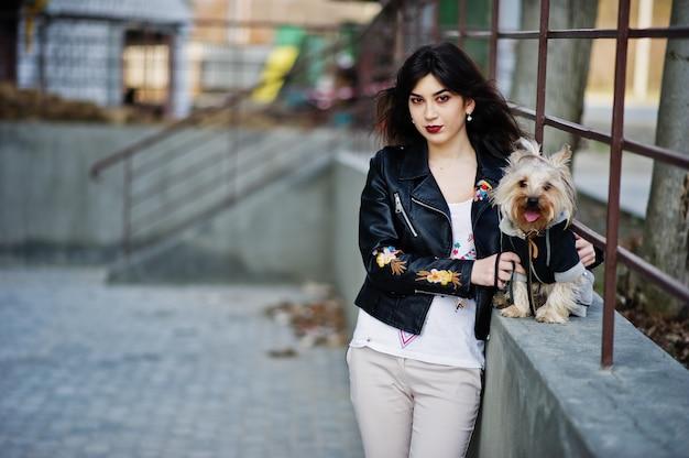 La ragazza zingara castana con il cane dell'yorkshire terrier ha proposto contro le inferriate d'acciaio. modello indossa giacca di pelle con ornamento, pantaloni.