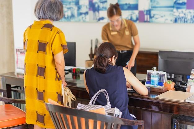 La reception della donna all'hotel che indossa la visiera con la donna effettua il check-in in hotel.