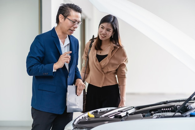 La receptionist asiatica apre il cofano dell'auto per controllare e spiegare l'elenco di base della manutenzione ai clienti presso il centro servizi di manutenzione
