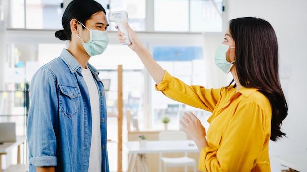 La receptionist femminile asiatica che conduce la maschera protettiva antiusura usa un termometro a infrarossi o una pistola termica sulla fronte del cliente prima di entrare in ufficio. stile di vita nuovo normale dopo il virus corona.