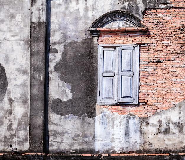 La retro vecchia finestra invecchiata d'annata e colore marrone hanno strutturato la parete del blocchetto del mattone dell'argilla