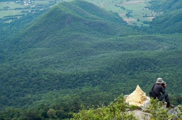 La retrovisione degli uomini che si siedono sulla scogliera e prende una foto contro la montagna e l'albero