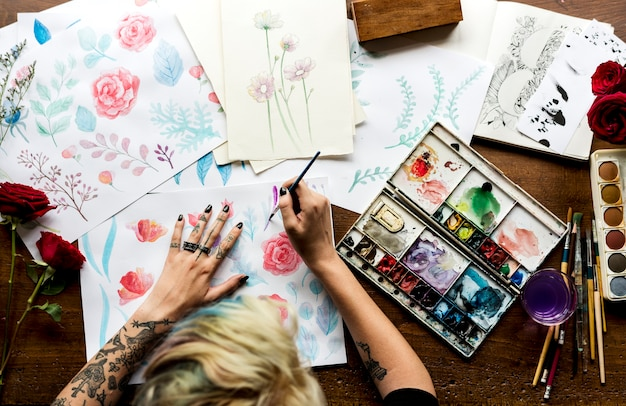 La retrovisione della pittura di lavoro della donna dell'artista fiorisce il colore dell'acqua sulle carte