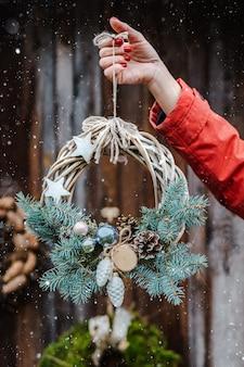 La retrovisione di giovani pantaloni a vita bassa femminili decorano la casa per il natale alla porta fuori. bella corona dell'albero di natale su vecchio fondo rustico di legno.