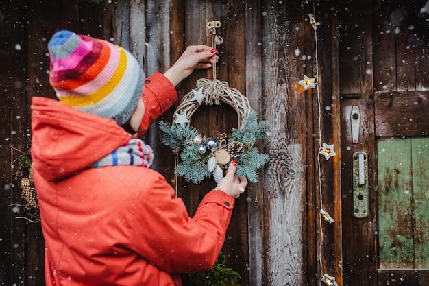 La retrovisione di giovani pantaloni a vita bassa femminili decorano la casa per il natale alla porta fuori. bella corona dell'albero di natale sulla vecchia parete rustica di legno.