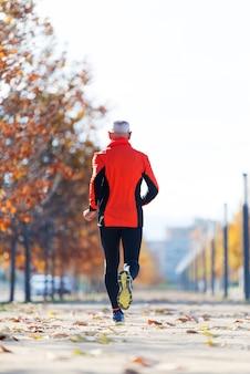 La retrovisione di un uomo senior nello sport copre fare jogging nel parco in un giorno soleggiato