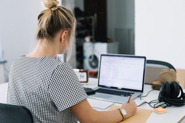 La retrovisione di una donna di affari scrive le note sopra carta marrone con il computer portatile sullo scrittorio