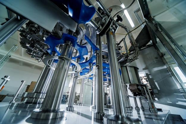La riempitrice automatica versa acqua in bottiglie di plastica in pet. produzione di birra.
