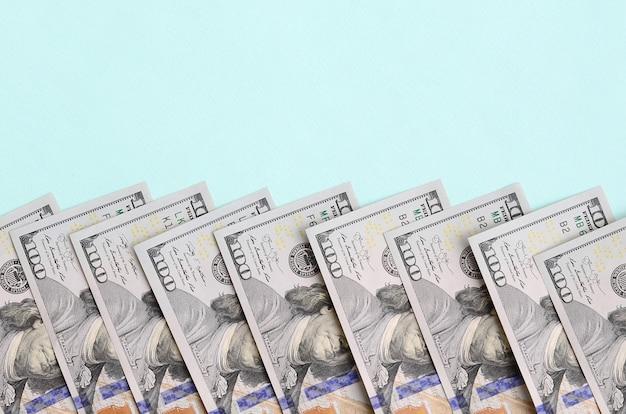 La riga delle fatture di un dollaro americano di nuovo disegno si trova su una priorità bassa blu-chiaro