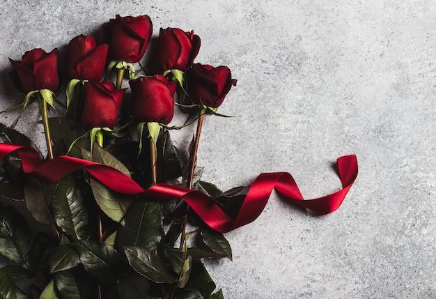 La rosa rossa di giorno di madri delle donne di giorno di biglietti di s. valentino con la sorpresa del regalo del nastro