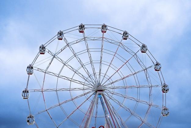 La ruota panoramica nel cielo blu si illumina per la guida serale