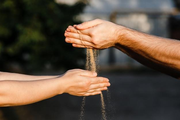 La sabbia viene riversata dalle mani degli uomini nelle mani delle donne.