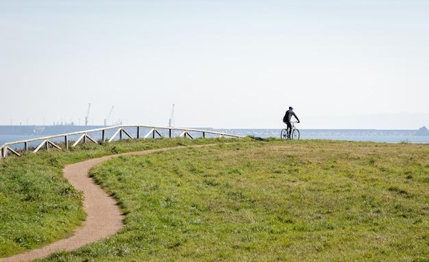 La sagoma del ciclista un uomo che cavalca in bicicletta in un parco con il mare in background.