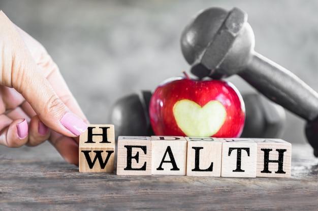 La salute è ricchezza con mela rossa e manubri