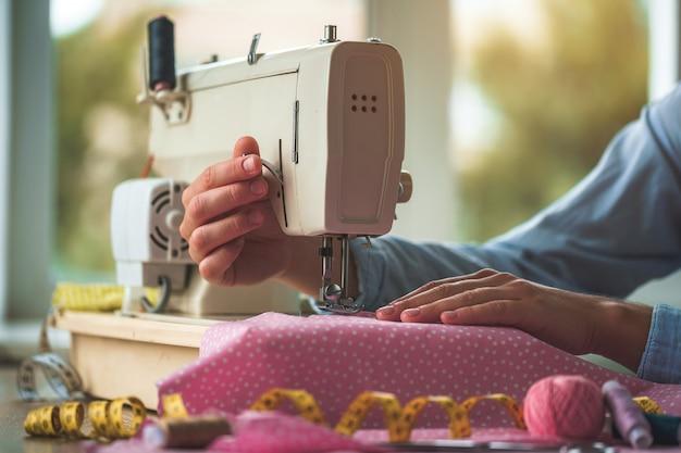 La sarta cuce i vestiti usando una macchina da cucire. processo di sartoria