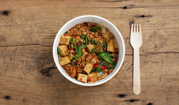 La scalpore tailandese della carne di maiale del basilico ha fritto con riso in scatola di carta dell'alimento