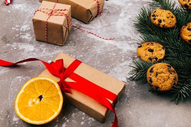La scatola attuale con il nastro rosso si trova sul pavimento grigio prima del ramo dell'abete con i biscotti