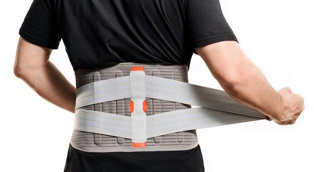 La schiena di un uomo in un corsetto ortopedico.