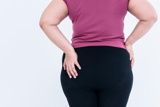 La schiena di una donna grassa che mette la mano sinistra sui fianchi che è grande e piena di grasso in eccesso