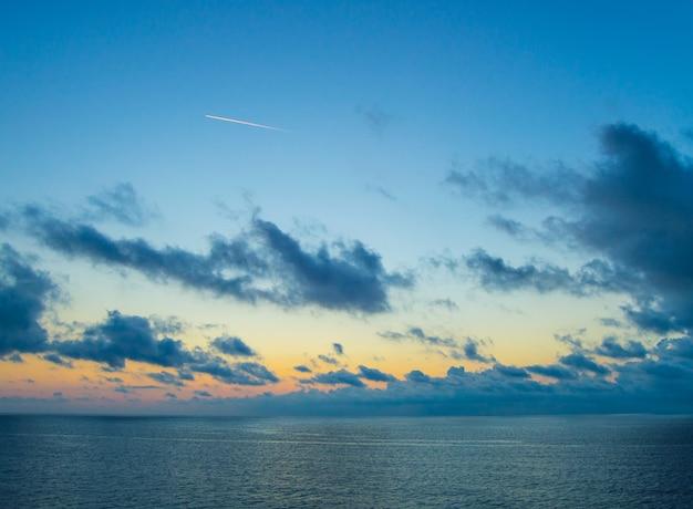 La scia di un jet sul mare sullo sfondo di un bellissimo tramonto dorato