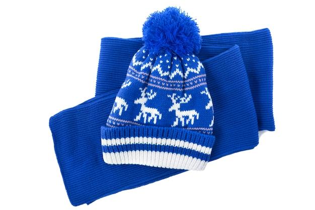 La sciarpa e l'inverno lavorati a maglia rossi bobble il cappello isolato su una priorità bassa bianca