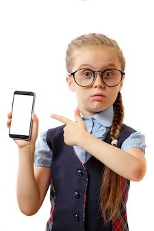 La scolara della bambina con i vetri tiene le mani del telefono con un gesto della mano e indica lo smartphone