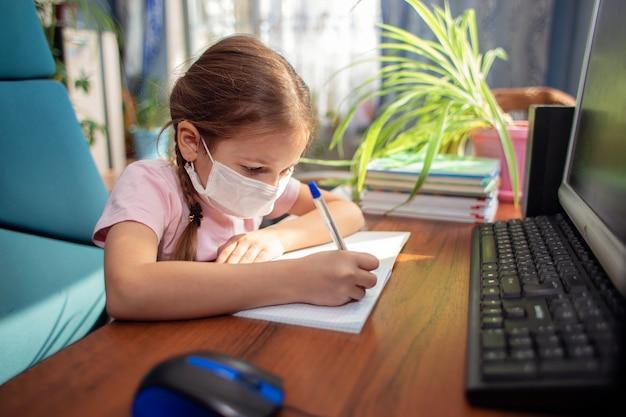 La scolara della ragazza in una mascherina medica fa i compiti davanti ad un computer. quarantena e apprendimento a distanza